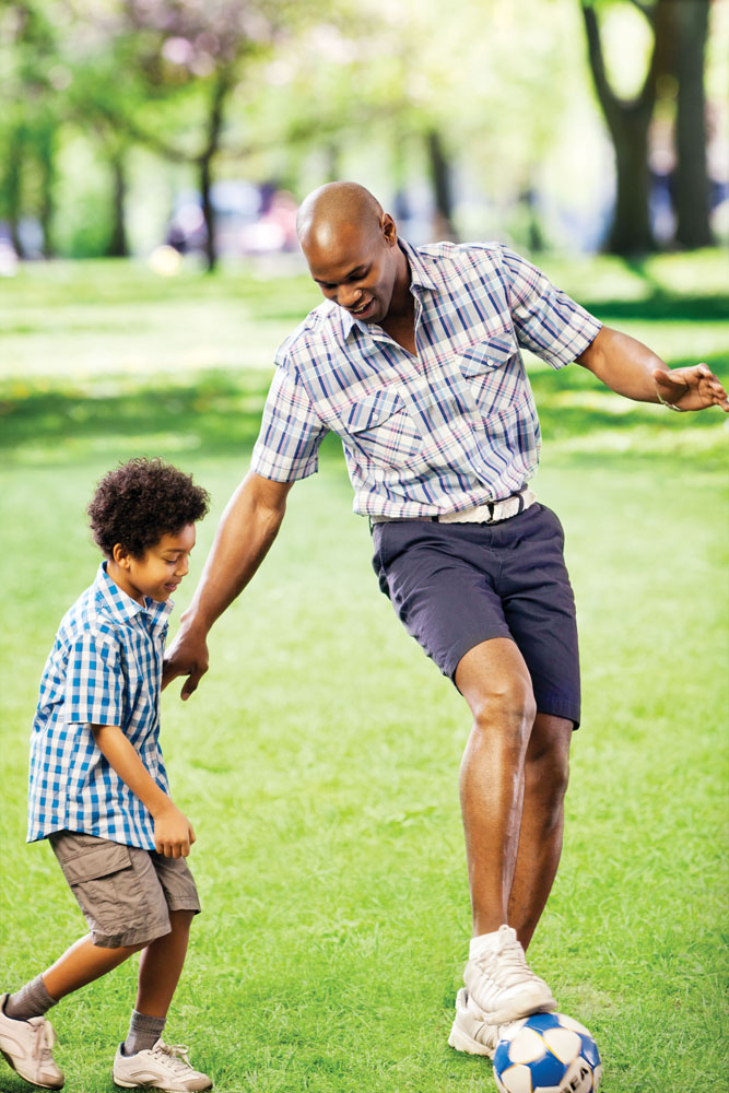 dad and son playing soccer in park